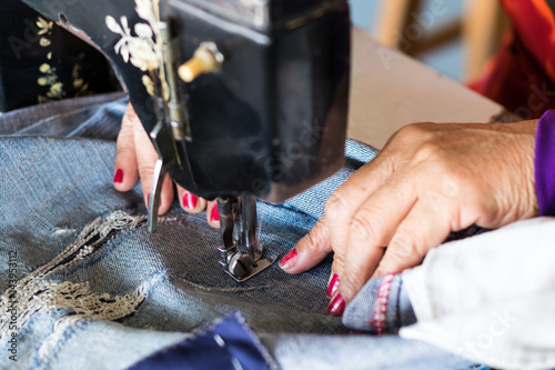 Red nail hand sewing jeans repair