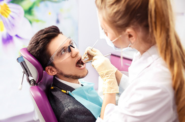Portrait of male. smile face. Dental care Concept. Dental inspection is being given to Beautiful man surrounded by dentist and his assistant