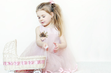 Little happy child girl in a white dress with a bow smiling shyly at a pink background copyspace