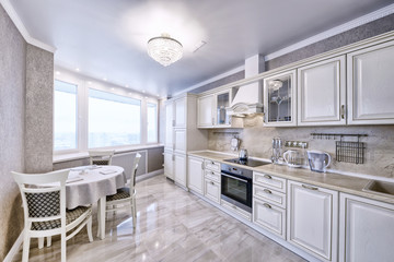 Interior of white wooden kitchen in a spacious apartment in light colors.
