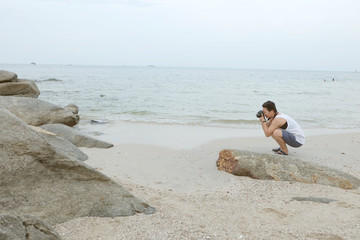 young man taking a photo bt the sea in the beach