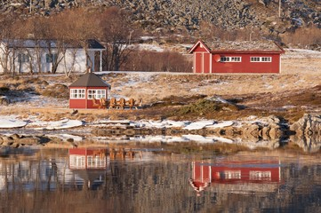 Some rorbuer reflected on the water of the near fiord in the Lofoten Islands, Norway.