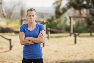 Fit woman standing with arms crossed in boot camp