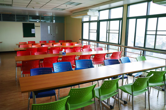 many color chairs with wood table in cafeteria.