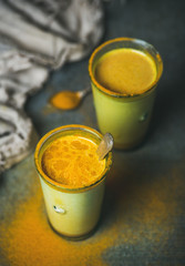 Golden milk with turmeric powder in glasses over dark background. Health and energy boosting, flu remedy, natural cold fighting drink. Clean eating, detox, weight loss concept