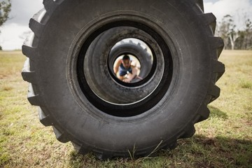 Man crawling through the tire during obstacle course