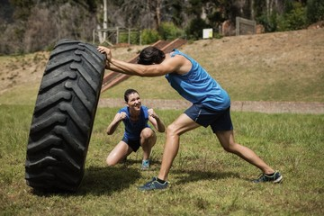 Fit man flipping a tire while trainer cheering
