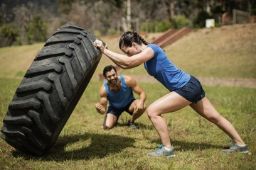 Fit woman flipping a tire while trainer cheering
