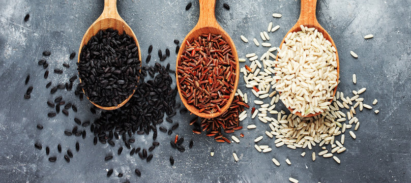 Collection of exclusive rice in wooden spoons - brown rice, red rice, black rice