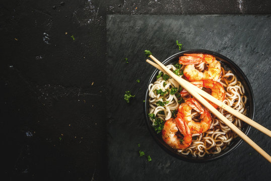 Asian soup with noodles (ramen), with miso paste, soy sauce, greens and shrimps prawn. On a black stone table, with chopsticks. Copy space top view