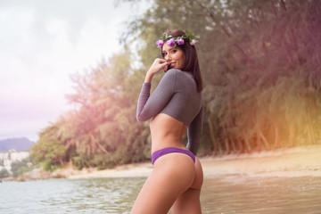 Sensual brunette woman wearing gray long sleeve top, purple underwear bottom and wreath looking into the camera and smiling while standing on the sandy beach over beautiful tropical island background