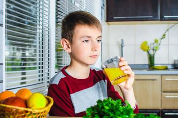 Teen drinking juice in the kitchen