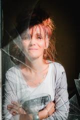 Femme derrière la vitre cassée de la maison abandonnée