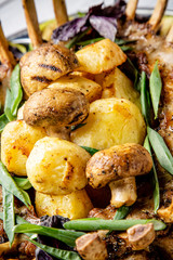 Grilled potatoes and mushrooms with meat and herbs close up