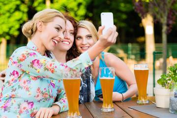 Freundinnen machen ein Selfie im Biergarten