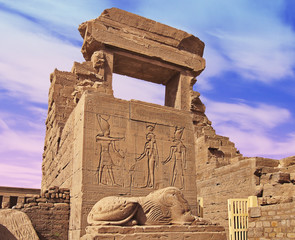 Remains of an Egyptian temple with a statue in the foreground and a blue sky with clouds in the background. Dendera, Egypt.