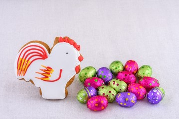 Stick cock souvenirs  and eggs decorative colored on a light background of natural linen tablecloths