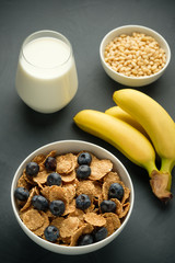 Healthy food. Milk, multi grain flakes with blueberry, nuts and bananas for breakfast.