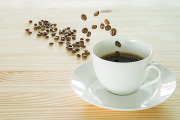 Coffee beans jumping into a white coffee cup on the wooden table