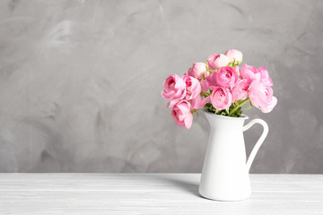 Vase with beautiful bouquet of ranunculus flowers on table