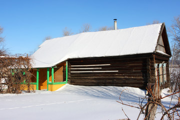 Wall Mural - Very old log house in the remote Russian village in the winter against a blue sky