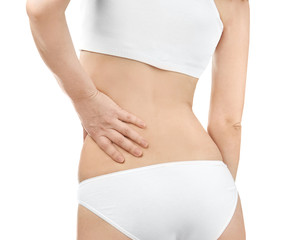 Young woman suffering from back pain on white background, closeup