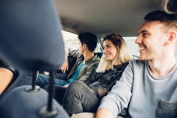 Group of friends multiethnic millennials view from automobile window traveling by car - togetherness, interaction, car sharing concept