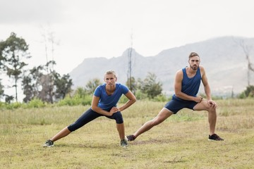 Fit man and woman exercising in boot camp