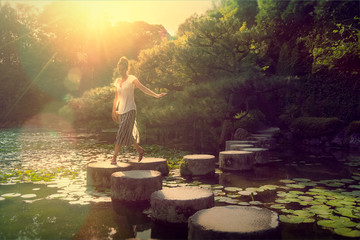 Young woman stepping on lake stone path in Kyoto Japan at sunset