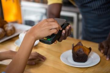 Customer paying barista through smart phone in coffee shop