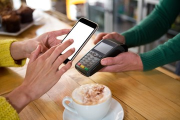 Barista accepting payment through smart phone