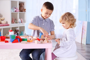 Cute little sister and brother playing with toy blocks at home