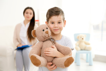 Little boy with teddy bear and child psychologist on background