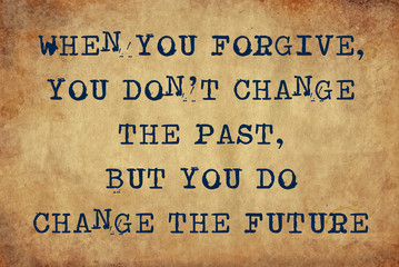 Inspiring motivation quote of when your forgive, you don't change the past, but you do change the future with typewriter text. Distressed Old Paper with Typing image.