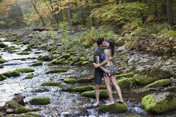 Young couple kissing while standing on rock  in stream