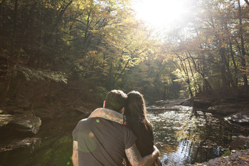 Rear view of young couple sitting near stream at forest