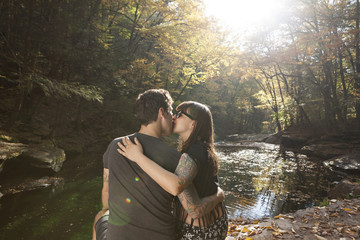 Young couple kissing while sitting near stream in forest