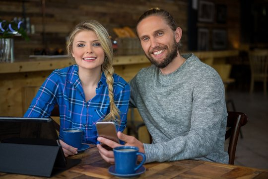 Portrait of smiling couple with coffee and technologies in cafe