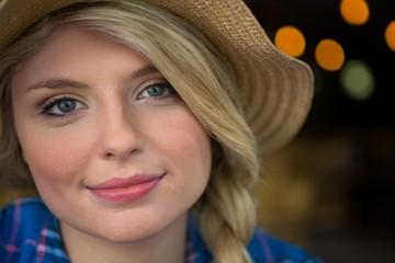 Portrait of woman wearing hat in coffee shop