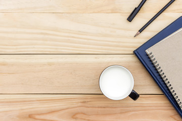 cup of milk and book on wooden table with soft-focus in the background. over light. style rustic.