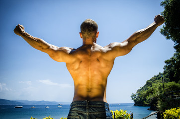 Back of young muscle man at the seaside, outdoors, showing muscular back and shoulders in front of the sea