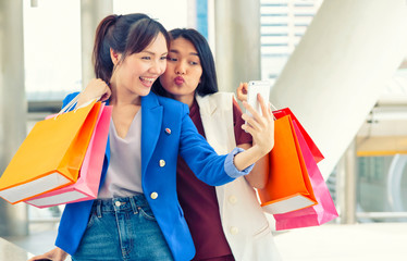 Two Asian woman taking selfie with smartphone while holding shopping bags in the shopping mall