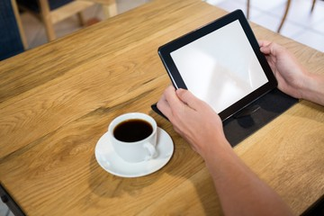 Cropped image of man using digital tablet in cafe