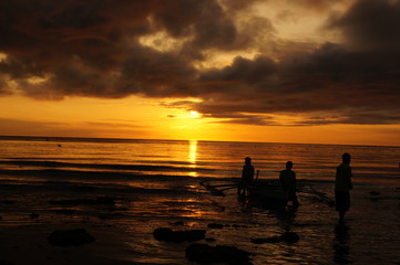 Sailing boats on the horizon and silhouette of lovely couple against a beautiful sunset on tropical exotic white beach