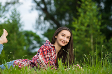 woman in jeans and shirt resting. Lays on the fresh grass