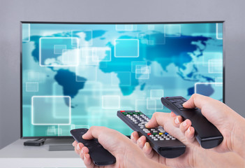 Hands holding multimedia remote control with smart TV