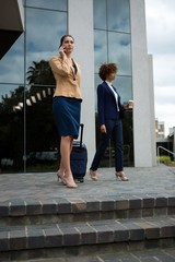 Businesswoman with luggage bag talking on mobile phone