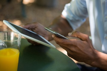 Man holding mobile phone and digital tablet at restaurant
