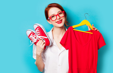 photo of beautiful young woman holding shirt on hanger and gumshoes on the wonderful blue studio background