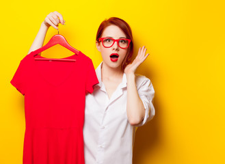 photo of beautiful young woman holding shirt on hanger on the wonderful yellow studio background